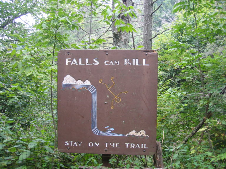image of sign that reads falls can kill stay on the trail