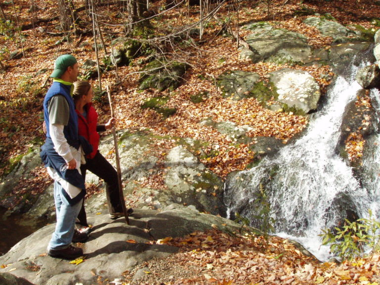 Joe and Kelly Fisher hiking by a stream in Shenandoah National Park