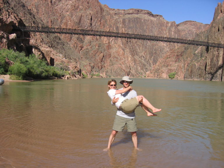 Joe and Kelly Fisher standing in the Colorado with the Black Suspension Bridge in the background
