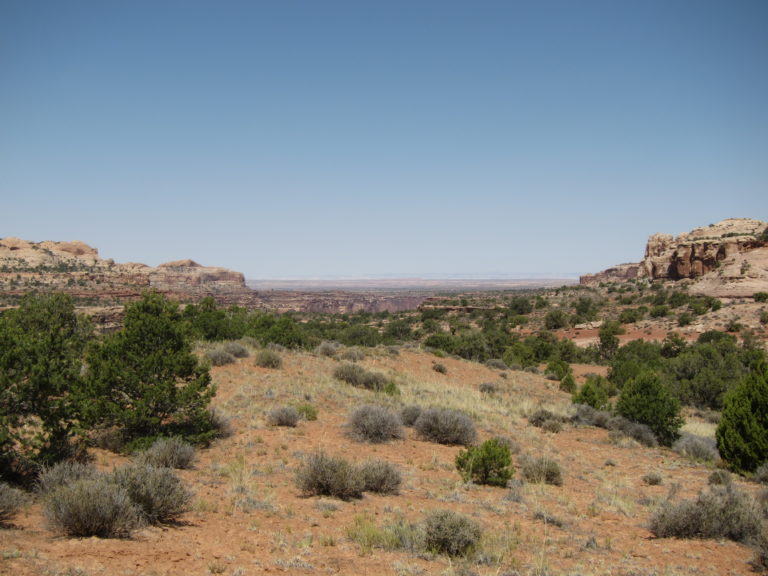 an open view of the distant desert between two canyon walls