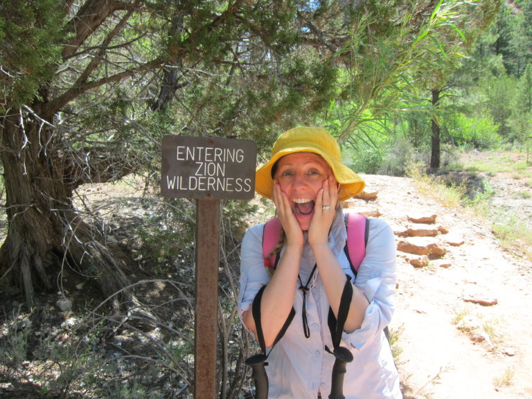 Kelly Fisher pretending to be scared in front of a sign that reads Entering Zion Wilderness