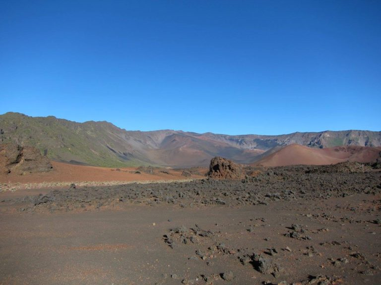gray and red rocks against green and gray ridges in Haleakala Crater