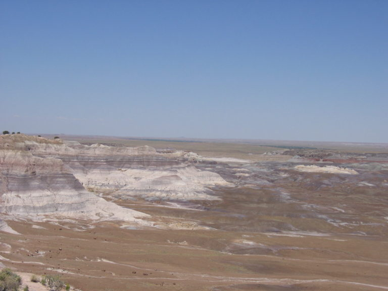 gray white green red and purple badlands in the open desert