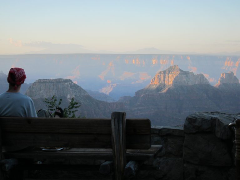 Joseph P. Fisher sitting on a bench at sunrise on the North Rim