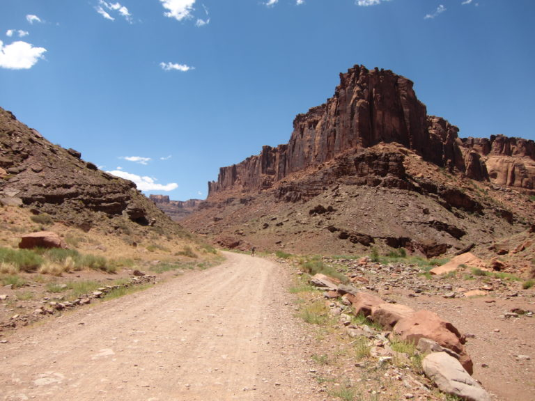 Joseph P Fisher small against large chocolate canyon wall on Long Canyon Road