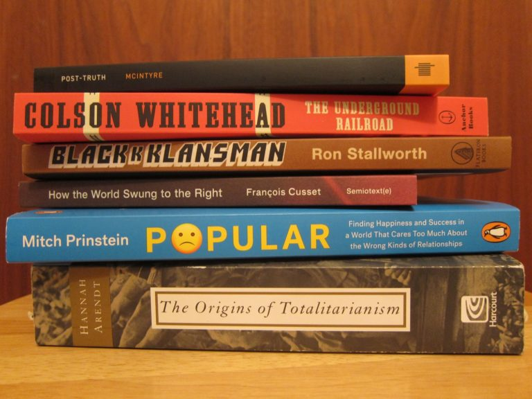 a stack of six paperback books on a wooden stool