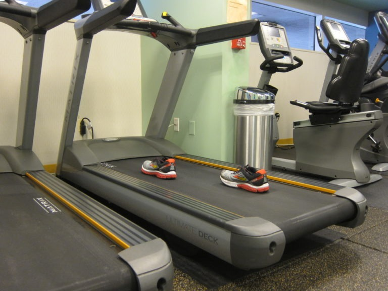 two red black and yellow running shoes on a treadmill